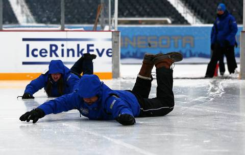 Rink workers Andrew Harris, foreground, and Amanda Paul slide onto a newly-resurfaced ice rink in Soldier Field.