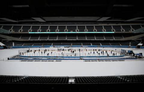 Many people take advantage of free ice skating as they glide around the ice rink constructed in the middle of Soldier Field as part of OfficeMax Hockey City Classic Winter Festival.