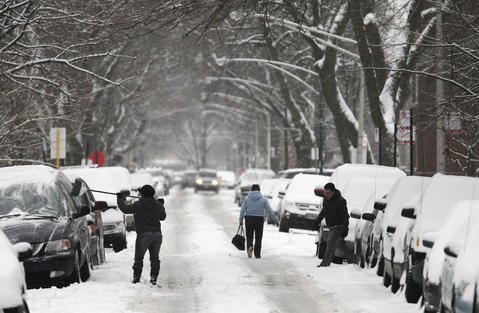 A woman sweeps the snow off of a car in the 3400 block of North Monticello Avenue in Chicago on Monday.