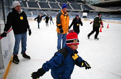 Brock Chiovari, 7, skates around an ice rink constructed in the middle of Soldier Field while his father Flint, left, watches as part of the Office Max Hockey City Classic Winter Festival in Chicago. The rink is in place for two college games on Feb. 17: University of Notre Dame vs. Miami University and University of Minnesota vs. University of Wisconsin.