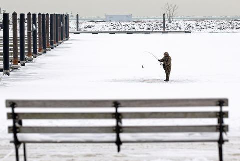 An angler catches a fish on the ice at DuSable Harbor today in Chicago.
