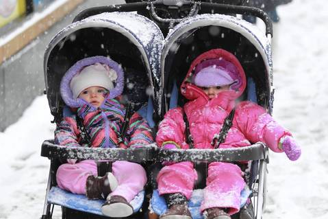 Sadie Migdal (left) and Margo Dameron (right), both one year old, are bundled up as they are escorted along Granville Avenue east of Broadway Street.