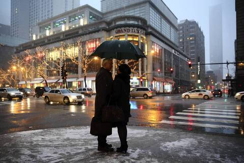 Mike McCahon and Karen Zupko share a moment before crossing Michigan Avenue as snow falls in Chicago.