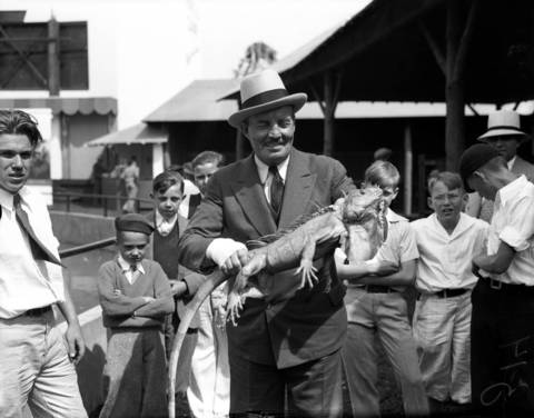 "Frank Buck holding a central American iguana, June 13, 1934. Frank Buck was an actor, collector of wild animals, and author, most famous for the book ""Bring 'Em Back Alive."""