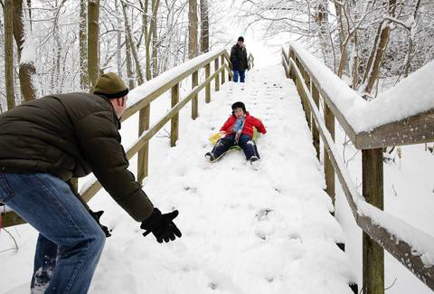 Daniel Hill, left, of Highwood, gets ready to catch his son Silas Hill, 6, during a sledding run at Moraine Park in Highland Park after an overnight snow storm. Hill's father-in-law Finlay Nicholson, of Asheville, N.C., waits above.