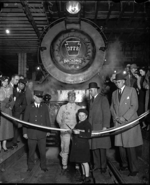 Child actor Jackie Cooper cuts the ribbon just before the departure of the Broadway Limited on its initial eighteen-hour run from Chicago to New York, April 25, 1932. Cooper had a successful acting career until retirement in 1989. Cooper also compiled one of the most distinguished peacetime military careers of anyone in his profession. In his industry, only James Stewart held a higher uniform rank in the U.S. Military.