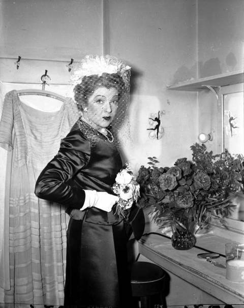 "Actress Ina Claire, who played the lead role in ""The Fatal Weakness"", gets ready for a costume change in her dressing room at Selwyn Theater in April 1947. (The Selwyn Theater and Harris Theater were redesigned and currently house the Goodman Theater)"