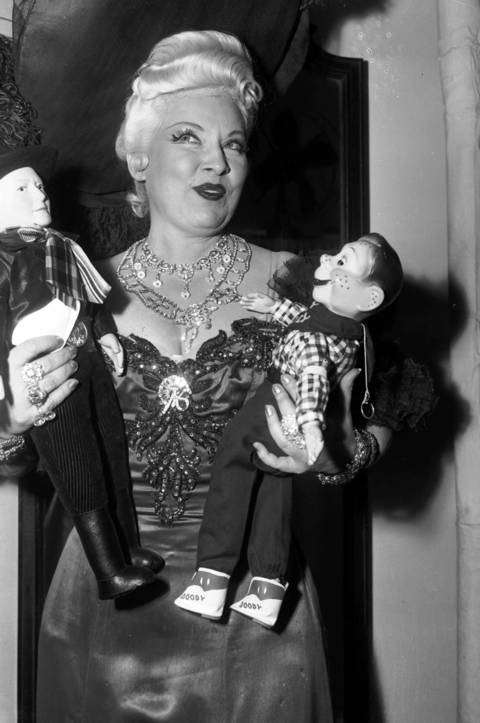"""A dame that knows the ropes isn't likely to get tied up."" Actress Mae West holding Howdy Doody dolls in Chicago, Dec. 12, 1951."