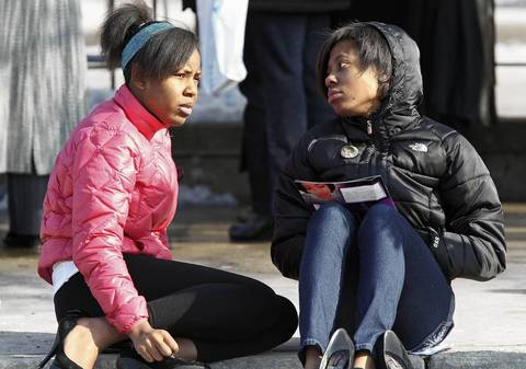 Teenagers sit outside the Greater Harvest Missionary Baptist Church during the funeral of Hadiya Pendleton. About 10:15 a.m., the funeral director came out and announced to the hundreds still waiting in line that no one else would be allowed inside -- not for the viewing or the funeral.