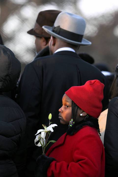 A girl holds a flower as 15-year-old Hadiya Pendleton is laid to rest at Cedar Park Cemetery in Riverdale.