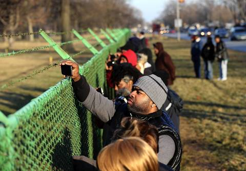 Onlookers take in the scene along the fence line at Cedar Park Cemetery in Riverdale as Hadiya Pendleton is buried.