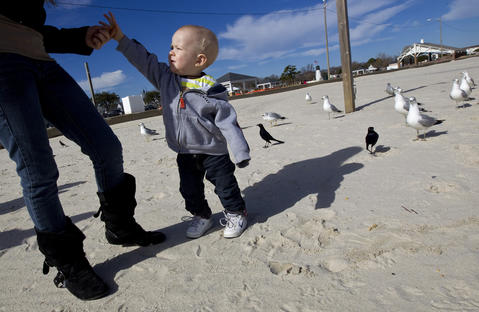 One-year-old Hayden Kelly gets a french fry from Tammie French to feed the seagulls at Buckroe Beach on Tuesday afternoon.