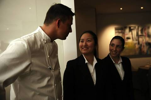 Chef Curtis Duffy, left, is greeted in the dining area during opening night at Grace.
