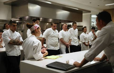 Curtis Duffy talks with his kitchen staff at the end of opening night at Grace.