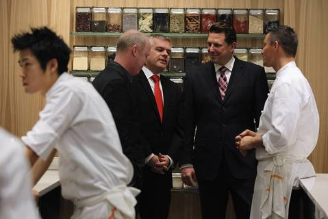 Michael Muser, second from right, and Curtis Duffy, right, give patrons a tour of the kitchen during opening night at Grace.