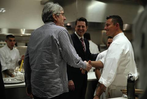 Michael Muser, center, and Curtis Duffy, right, give a tour of the kitchen to Cliff Colnot, a regular patron since Duffy's days at Avenues restaurant, during opening night at Grace.