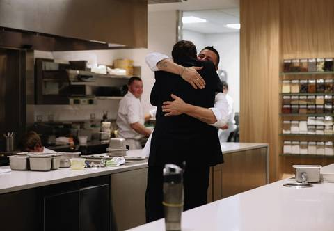 General manager and restaurant partner Michael Muser, back to camera, hugs Curtis Duffy during opening night at Grace.