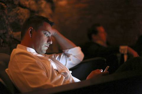 After a long opening night, Curtis Duffy reads his emails in the lounge under the restaurant.