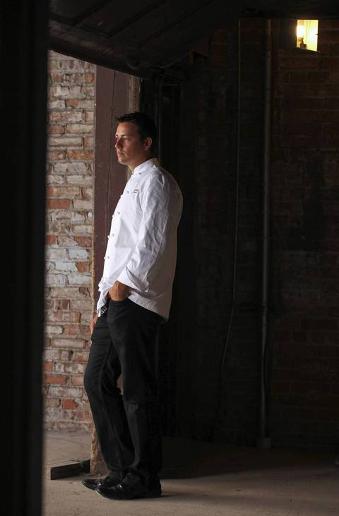 Curtis Duffy, who worked under Charlie Trotter, stands on the loading dock of his new restaurant Grace in August, while it was still under construction.
