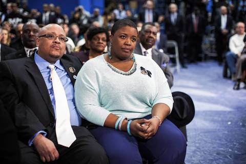 Cleopatra Cowley-Pendleton and Nathaniel Pendleton Sr. listen to President Barack Obama as he delivers remarks at Hyde Park Academy in Chicago. The Pendleton's 15-year-old daughter, Hadiya, was killed by gunfire while standing in a park about a mile from President Obama's Kenwood home.