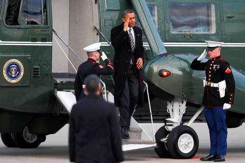 President Barack Obama salutes as he leaves Marine One before departing from O'Hare International Airport to Washington DC. He spoke at Hyde Park Academy in Chicago about strengthening the economy for the middle class and gun violence.