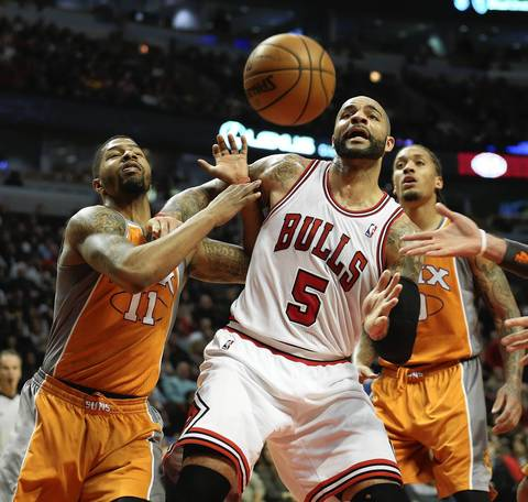 Carlos Boozer fights for possession of the ball with the Suns' Markieff Morris during the first half.