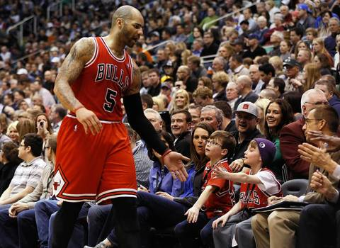 Carlos Boozer high-fives a fan on his way to the bench during the first half against the Jazz.