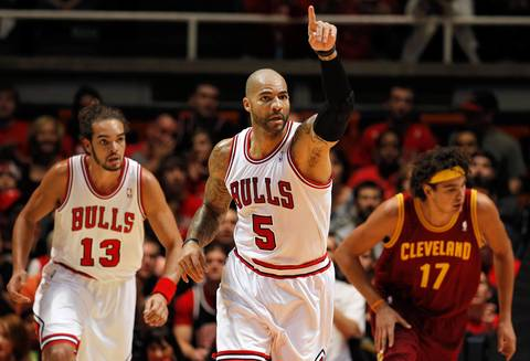 Carlos Boozer celebrates a basket against the Cavaliers' Anderson Varejao during a preseason game.