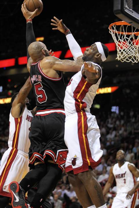 Carlos Boozer goes strong to the basket against the Heat's LeBron James during the 1st quarter.