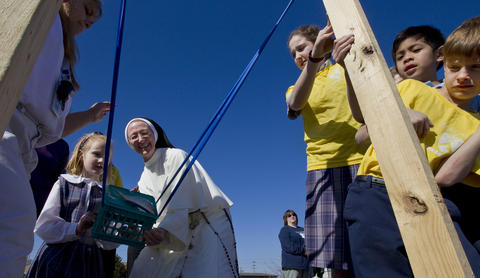 Julia Campbell and Sister Mary Amata use a slingshot to launch a fish to pelicans at the edge of Mill Creek at Saint Mary Star of the Sea School in Phoebus on Friday.
