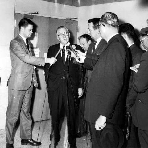 Secretary of State Paul Powell, center, answers questions from journalists as he leaves the DuPage County Courthouse after appearing before the Grand Jury for questioning on October 10, 1966. Powell's office was investigated for corruption in 1966, but Powell was exonerated.