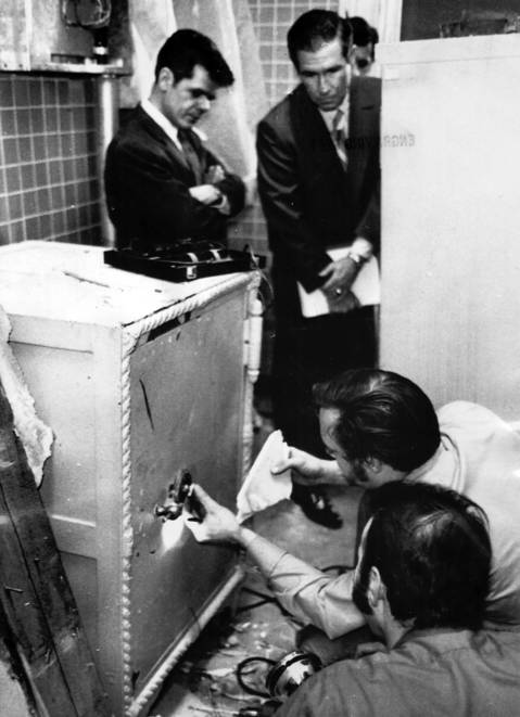 Sangamon County State's Atty. Richard Hollis, left, and Asst. Atty. General Waldo Ackerman look on as locksmiths try to open one of three safes found in the original offices of former Secretary of State Paul Powell in Springfield on January 21, 1971.
