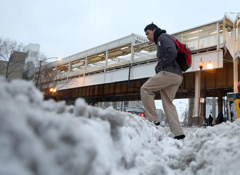 A man steps over slushy snow on the corner of Western and Milwaukee Avenues.