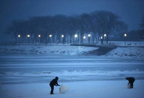 Alex Davila and Nick Eby build snow sculptures next to Lake Michigan at Ohio Street Beach in downtown Chicago.