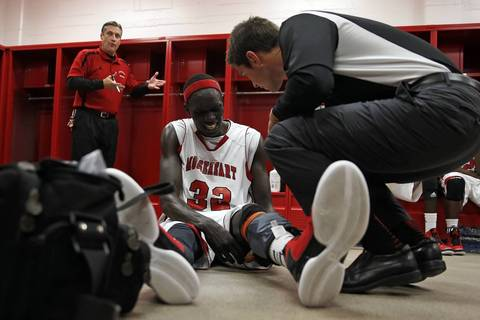 As coach Ron Ahrens talks, Mooseheart's Makur Puou deals with a knee injury at half time of 70-67 loss to Chicagoland Jewish during IHSA Class 1A sectional semifinal.
