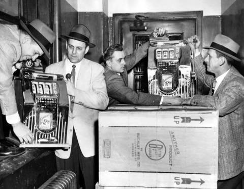 Detectives unload confiscated slot machines at the department bureau on March 12, 1958. They seized 60 machines from Buckley Manufacturing Company Inc. located at 4223 Lake Street, Chicago. From left are Detective Leonard Hanlon, Det. Albert Kokusk, Det. George Volk, and Det. James Lannon.