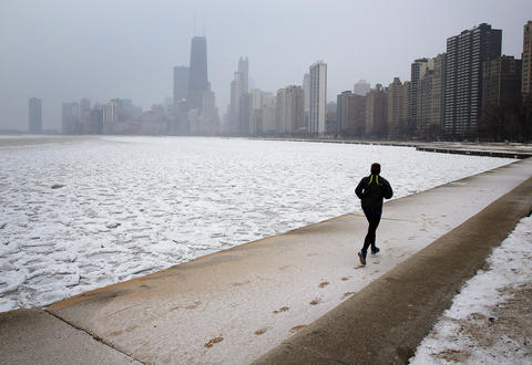 A jogger leaves tracks in the snow along the lakefront.