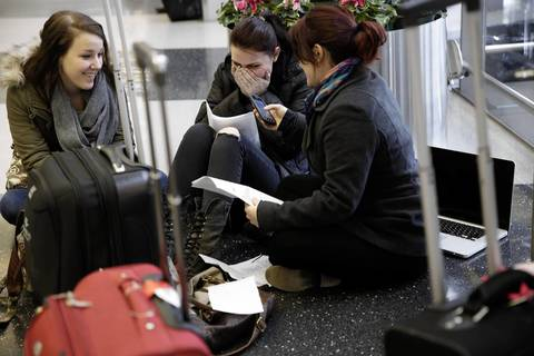 Loyola University students Samantha Shaffer, 19, left, Yelena Svetlichnaya, 20, center, and Tala Said, 19, react to a dropped customer service call as they try to reschedule flights to Toronto at O'Hare International Airport.