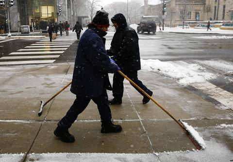 Custodians scrape the walks at Michigan Avenue and Pearson Street.