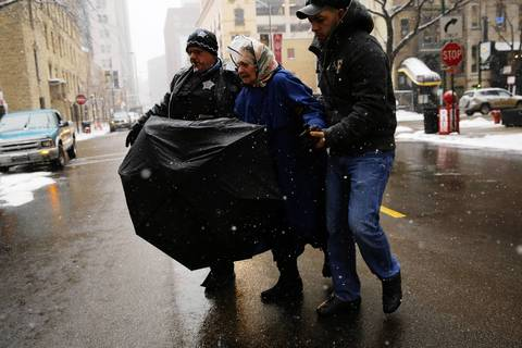 Chicago Police Officer Charlie Bant, left, and passerby Haldo Zamora, right, from East Chicago, Ind., help an elderly woman across the street after she fell in the snow.