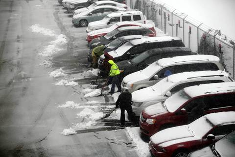 Crews remove snow from cars in the Avis rental car lot at O'Hare International Airport.