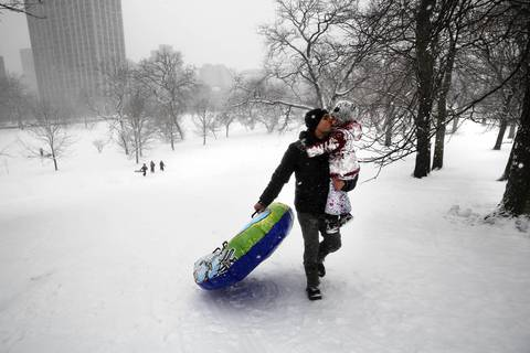 Marius Grigore gives his daughter Ariadna, 4, a big kiss on the cheek as he carries her and their inner tube back up the hill in Lincoln Park to go sledding.