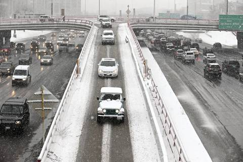 Drivers negotiate snowy conditions on the Kennedy expressway at Randolph Street.
