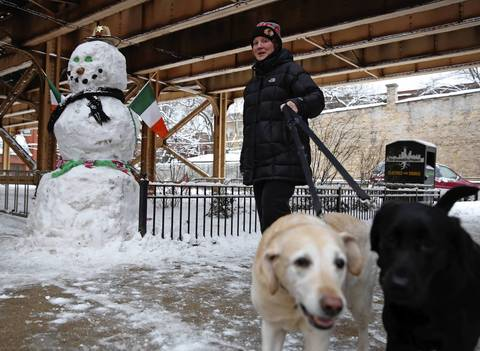 A woman walks her dogs past a snowman with Irish theme in Lincoln Park.