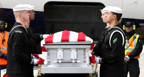 A Navy ceremonial guard removes the remains of a sailor that served on the USS Monitor after they arrived a Dulles International Airport Thursday. The remains will be interred Friday at Arlington National Cemetery.