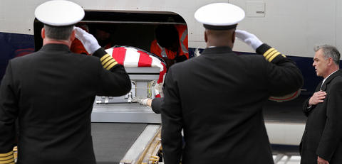 The escorts for the remains of two sailors killed when the USS Monitor sank off the North Carolina coast render salutes at the casket is removed from a commercial flight at Dulles International Airport Thursday. The two sets of remains will be laid  to rest in Arlington National Cemetery Friday with full military honors. No Mags, No Sales, No Internet, No TV
