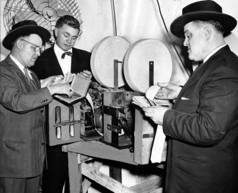 Detectives John Hastings, from left, James Flynn, and Timothy Allman from the police commissioner's office inspect printing presses and other policy wheel equipment in the Rosedale Poultry Shop at 3850 South Park Way in January of 1953.
