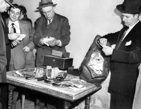 State's Attorney's policemen look over pistols, ammunition, small coins, a traveling bag full of money and policy sheets which were taken in a raid of Nick Manno's home at 1038 S. Sangamon, Chicago on March 15, 1951.