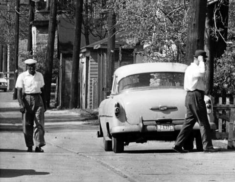 A policy runner walks over to the front seat of a car to make a pickup in an alley at 69th and State Street, Chicago, Ill, in May 1964.