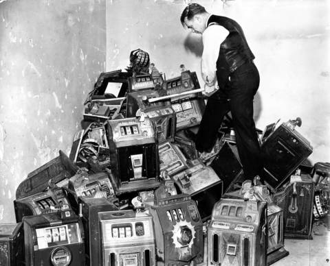 Sgt. John Healy of the county highway police hacks into 50 slot machines with a sledgehammer that were seized in raids in Cook County in February 1939. The machines were taken to the basement of the county building to be destroyed.